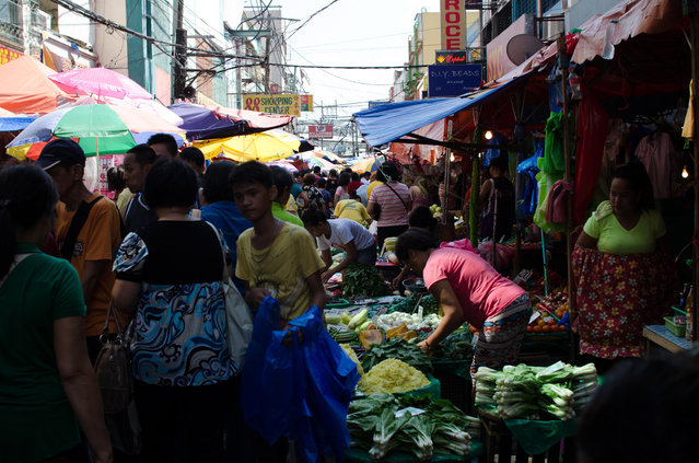 Residents walk through a downtown market area, as shoppers buy produce from a vegetable stall, on August 11, 2014 in Manila, Philippines. (Photo by Dondi Tawatao/Getty Images)