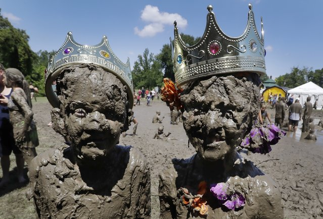 Aiden Haas, left, and Lilli Alcala pose after being crowned Mud King and Mud Queen at the 29th annual Mud Day, Tuesday, July 12, 2016 in Westland, Mich. The event, open to children 12 and younger, was at the Hines Park-Nankin Mills Area west of Detroit. Children 12 and younger were able to slosh around in the pit while participating in mud limbo, wheelbarrow races and other free activities. (Photo by Carlos Osorio/AP Photo)