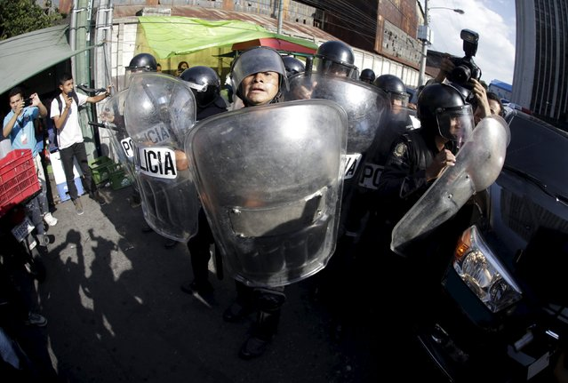 Riot police officers confront the media as they attempt to take pictures and videos of former Guatemalan Vice President Roxana Baldetti in her vehicle as she leaves her hearing in Guatemala City, Guatemala, August 25, 2015. Baldetti today was linked to criminal proceedings on charges of conspiracy and fraud, a number of corruption investigations have devastated the President Otto Perez's cabinet and led to her resignation in May. (Photo by Jorge Dan Lopez/Reuters)