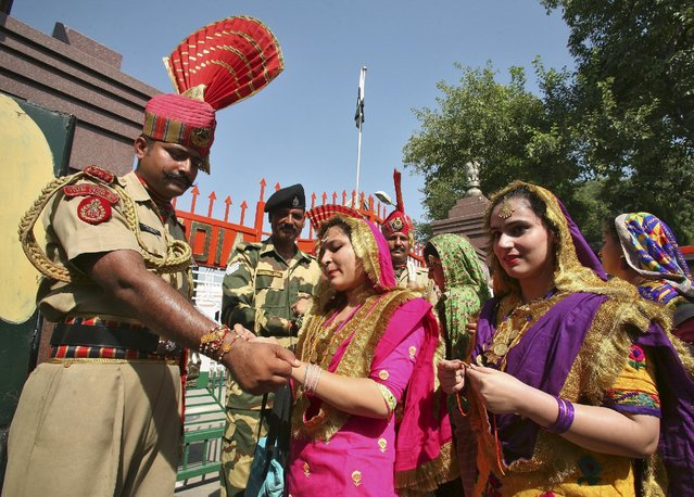 "An Indian woman ties a ""Rakhi"" or a traditional Indian sacred thread onto the wrist of Indian Border Security Force (BSF) soldier during the Raksha Bandhan celebrations at the India-Pakistan joint check post at the Wagah border on the outskirts of Amritsar, India, August 29, 2015. (Photo by Munish Sharma/Reuters)"