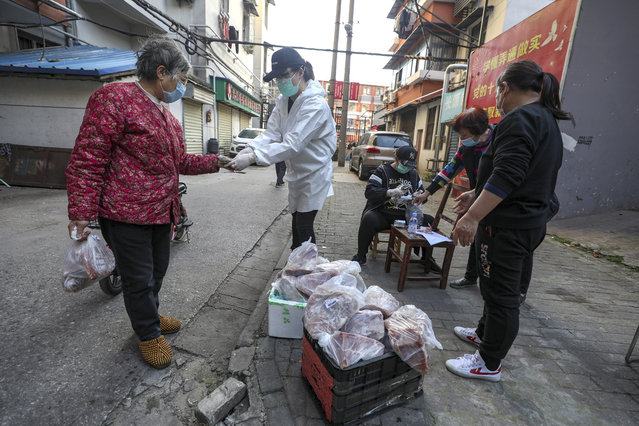 In this March 18, 2020 photo, people buy pork at the entrance gate of a closed residential community in Wuhan in central China's Hubei Province. Last month, Wuhan was overwhelmed with thousands of new cases of coronavirus each day. But in a dramatic development that underscores just how much the outbreak has pivoted toward Europe and the United States, Chinese authorities said Thursday that the city and its surrounding province had no new cases to report. The virus causes only mild or moderate symptoms, such as fever and cough, for most people, but severe illness is more likely in the elderly and people with existing health problems. (Photo by Chinatopix via AP Photo)