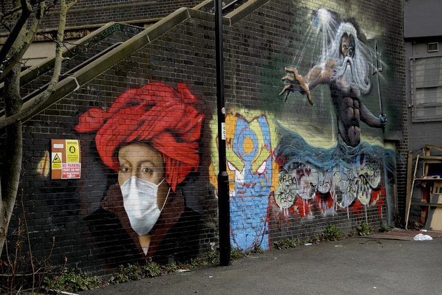 A mural by street artist Lionel Stanhope with a face mask reference to coronavirus next to one of his other works, at right, painted on a bridge wall in Ladywell, south east London, Thursday, April 2, 2020. (Photo by Matt Dunham/AP Photo)