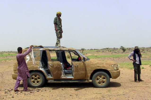 A fighter from the Coordination of Azawad Movements (CMA) stands on his vehicle covered in mud for camouflage outside Anefis, Mali, August 26, 2015. (Photo by Souleymane Ag Anara/Reuters)