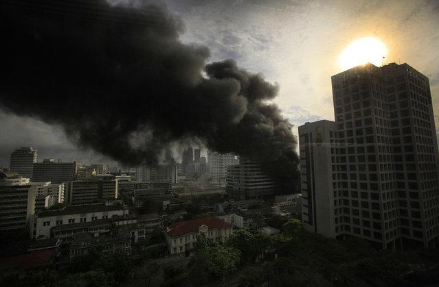 Thick black smoke plummets through the air behind the main Chulalongkorn hospital from anti-protesters' encampment on Wednesday May 19, 2010 in Bangkok, Thailand. (Photo by Wong Maye-E/AP Photo)