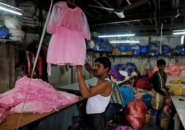 A worker conducts a final check on a dress inside a small-scale garment manufacturing unit in Mumbai, India, August 1, 2016. (Photo by Danish Siddiqui/Reuters)