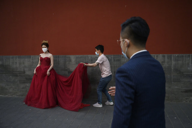 A photo assistant helps a woman with her dress as her future husband looks on while they wear protective masks while taking pictures in advance of their wedding near the Forbidden City, on April 30, 2020 in Beijing, China. Beijing lowered its risk level after more than three months Thursday in advance of the May holiday, allowing most domestic travellers arriving in the city to do so without having to do 14 days of quarantine. The Forbidden City will open to a limited number of visitors as of Thursday morning. After decades of growth, officials said China's economy had shrunk in the latest quarter due to the impact of the coronavirus epidemic. The slump in the world's second largest economy is regarded as a sign of difficult times ahead for the global economy. While industrial sectors in China are showing signs of reviving production, a majority of private companies are operating at only 50% capacity, according to analysts. With the pandemic hitting hard across the world, officially the number of coronavirus cases in China is dwindling, ever since the government imposed sweeping measures to keep the disease from spreading. Officials believe the worst appears to be over in China, though there are concerns of another wave of infections as the government attempts to reboot the world's second largest economy. Since January, China has recorded more than 81,000 cases of COVID-19 and at least 3,200 deaths, mostly in and around the city of Wuhan, in central Hubei province, where the outbreak first started. (Photo by Kevin Frayer/Getty Images)