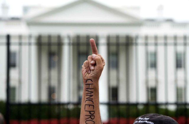 A protestor holds up a middle finger to the White House in Washington, DC, September 9, 2014. (Photo by Saul Loeb/AFP Photo)