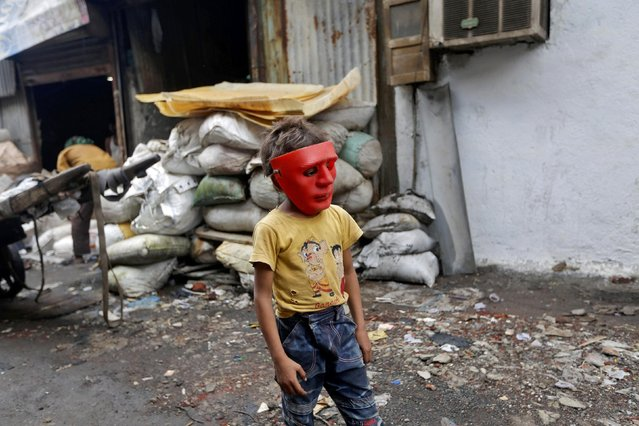 A boy wearing a plastic mask walks in an industrial area in Mumbai, India, August 3, 2016. (Photo by Shailesh Andrade/Reuters)