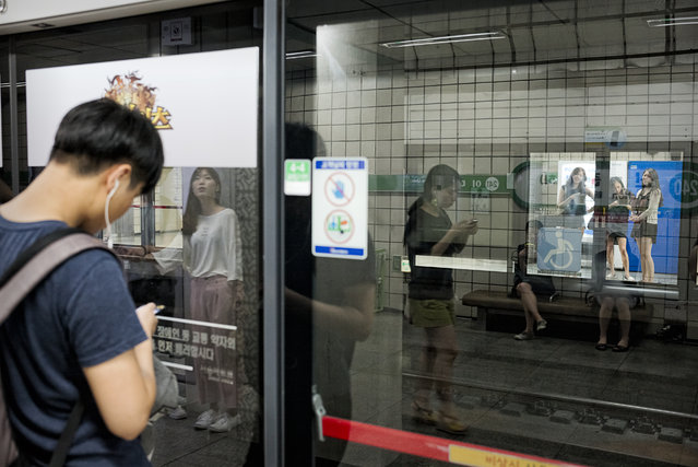 People wait for a subway train at a platform of Sinchon station on August 4, 2015 in Seoul, South Korea. An automated screen doors with advertisements and signs are installed in most of subway station in Seoul. (Photo by Shin Woong-jae/The Washington Post)