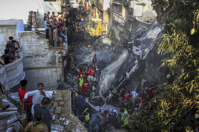 Volunteers look for survivors of a plane that crashed in a residential area of Karachi, Pakistan, May 22, 2020. An aviation official says a passenger plane belonging to state-run Pakistan International Airlines carrying nearly 100 passengers and crew crashed near Karachi's airport. (Photo by Fareed Khan/AP Photo)