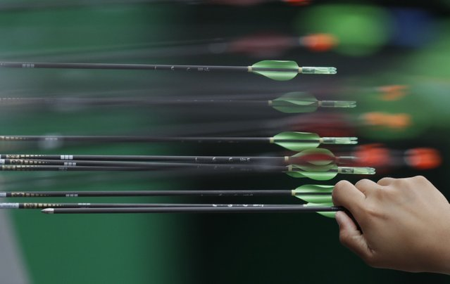 An archery athlete collects an arrow before the start of an elimination round of the individual archery competition at the Sambadrome venue during the 2016 Summer Olympics in Rio de Janeiro, Brazil, Wednesday, August 10, 2016. (Photo by Alessandra Tarantino/AP Photo)