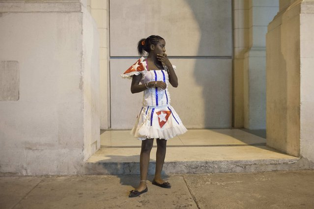 A dancer takes a break during the celebrations of the 54th anniversary of the creation of the Committees for the Defense of the Revolution (CDR) in Havana, September 28, 2014. The CDRs, created by former Cuban leader Fidel Castro, are assigned to every block of houses in Cuba, to provide medical assistance if needed, and to monitor people's movements and activities in each neighbourhood. (Photo by Alexandre Meneghini/Reuters)