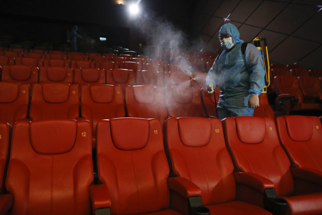 A staff member of a cinema sprays disinfectant at the cinema hall to prepare for reopening on July 1 in Kuala Lumpur, Malaysia, Friday, June 26, 2020. Malaysia entered the Recovery Movement Control Order (RMCO) after three months of coronavirus restrictions. (Photo by Vincent Thian/AP Photo)