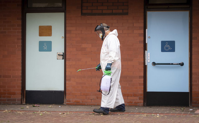 A worker for Leicester City Council disinfects public toilets in Leicester, England, Monday June 29, 2020. The central England city of Leicester is waiting to find out if lockdown restrictions will be extended as a result of a spike in coronavirus infections. (Photo by Joe Giddens/PA Wire via AP Photo)