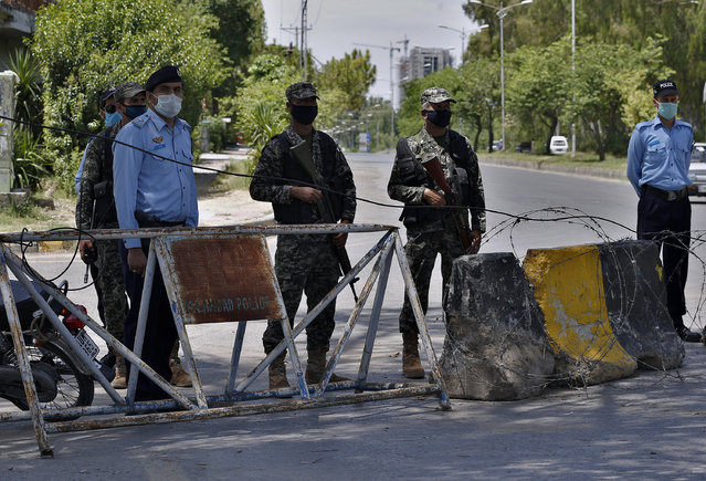 Pakistan paramilitary soldiers and a police officers stand guard at a checkpoint of a restricted area to help to contain the spread of new coronavirus, in Islamabad, Pakistan, Saturday, June 13, 2020. Capital administration sealed few areas of Islamabad following the decision taken on the advice of the Health Department and epidemiologists after hundreds of cases were reported from these areas. (Photo by Anjum Naveed/AP Photo)