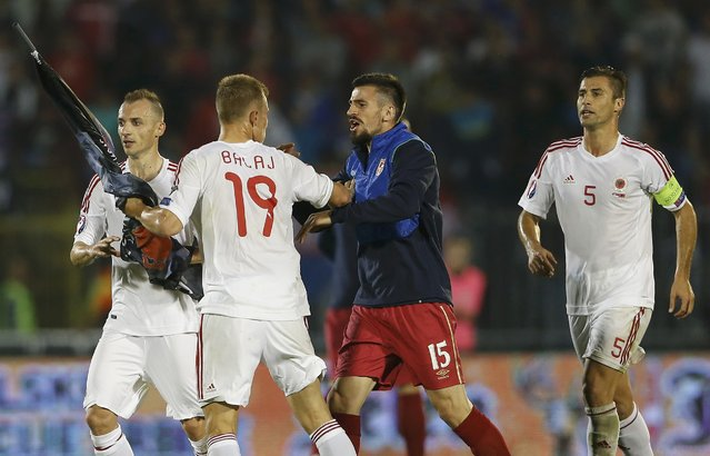 Nenad Tomovic (C) of Serbia argues with Bekim Balaj (2nd L) of Albania who carries a flag depicting so-called Greater Albania, an area covering all parts of the Balkans where ethnic Albanians live, after it was flown over the pitch during their Euro 2016 Group I qualifying soccer match at the FK Partizan stadium in Belgrade October 14, 2014. (Photo by Marko Djurica/Reuters)