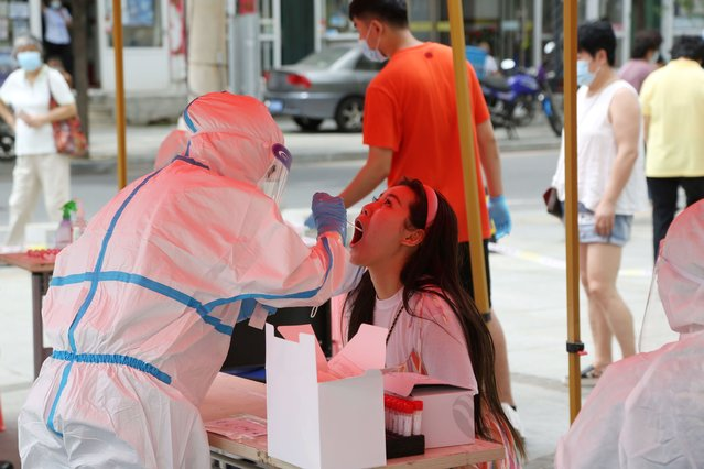 A health worker carries out a COVID-19 coronavirus test at a makeshift testing center in Dalian, in China's northeast Liaoning province on July 27, 2020. China recorded 61 new coronavirus cases on July 27 – the highest daily figure since April – propelled by clusters in three separate regions that have sparked fears of a fresh wave. (Photo by AFP Photo/China Stringer Network)