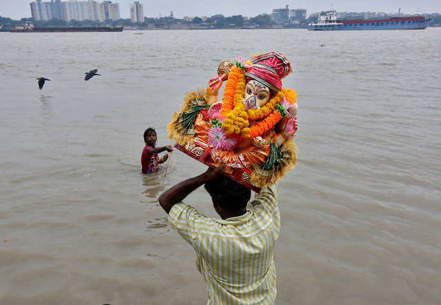 A devotee carries an idol of the Hindu god Ganesh, the deity of prosperity, for immersion in the waters of the river Ganges on the second day of the Ganesh Chaturthi festival in Kolkata, India, September 6, 2016. (Photo by Rupak De Chowdhuri/Reuters)