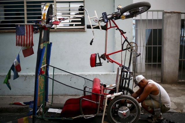 A man repairs his tricycle in Havana, September 18, 2015. (Photo by Edgard Garrido/Reuters)