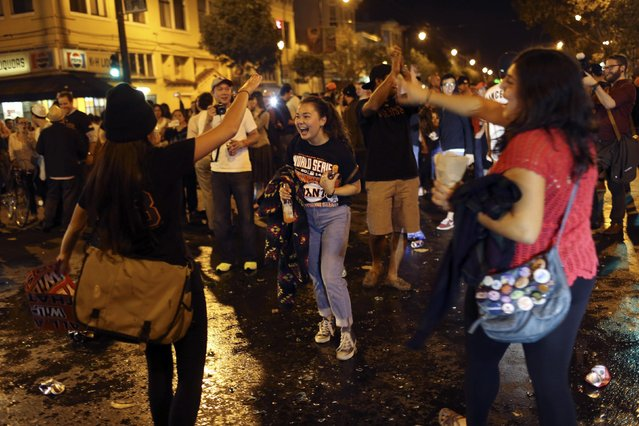 Fans celebrate on a street in the Mission District after the San Francisco Giants defeated the Kansas City Royals in Game 7 of the World Series, in San Francisco, California October 29, 2014. (Photo by Robert Galbraith/Reuters)