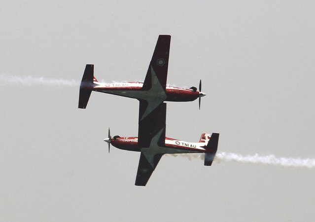 Two Wong Bee airplanes from the Jupiter Aerobatic Team of the Indonesian Air Force fly past each other during a rehearsal for the ceremony marking the 70th anniversary of Indonesia's military in Cilegon, Banten province, October 3, 2015. Indonesia will celebrate the anniversay of its military on October 5. (Photo by Reuters/Beawiharta)