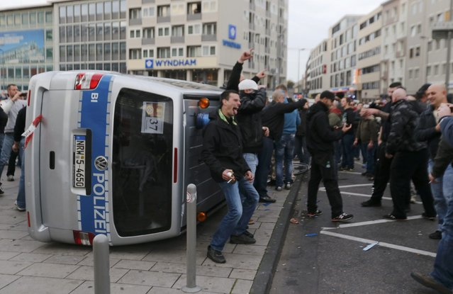 """A man poses for a photo next to an overturned police van during a demonstration by """"hooligans against Salafists and Islamic State extremist"""" in Cologne October 26, 2014. (Photo by Wolfgang Rattay/Reuters)"""
