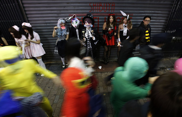 Participants, wearing make-up and costumes, eat candy during Halloween night in Tokyo's Shibuya district October 31, 2014. Thousands of costumed revellers descended on Shibuya crossing in downtown Tokyo on Friday to celebrate Halloween in what has in recent years become a incredibly popular Japanese past time. (Photo by Yuya Shino/Reuters)