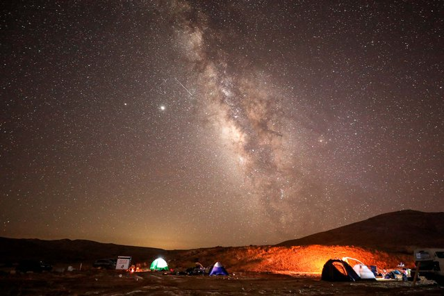A Perseid meteor streaks across the sky above a camping site at the Negev desert near the city of Mitzpe Ramon on August 11, 2020 during the Perseids meteor shower, which occurs every year when the Earth passes through the cloud of debris left by the comet Swift-Tuttle. (Photo by Menahem Kahana/AFP Photo)