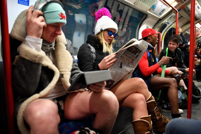 """People take part in the annual """"No Trousers On The Tube Day"""" (No Pants Subway Ride) on the Central line in London on January 7, 2018. (Photo by Ben Stansall/AFP Photo)"""