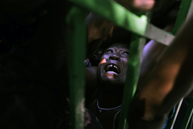 A woman is crushed in a crowd of people waiting for food rations in the aftermath of the January 12 earthquake in Port-au-Prince, Thursday, January 28, 2010. (Photo by Ramon Espinosa/AP Photo)
