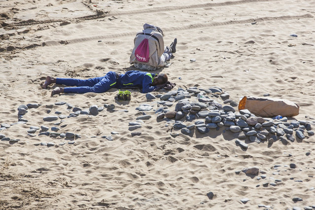 Two would-be immigrants rest at Maspalomas beach on Gran Canaria in Spain's Canary Islands, November 5, 2014. (Photo by Borja Suarez/Reuters)