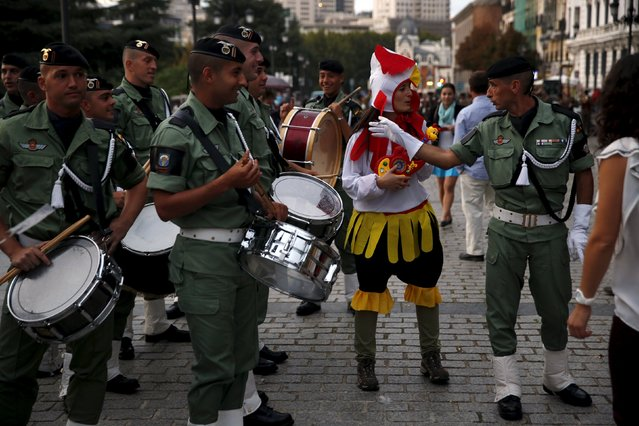 A woman in costume jokes with soldiers of Spanish armed forces as they wait to take part in a military music parade outside the Royal Palace in Madrid, Spain, October 10, 2015. Spain will mark its National Day with a military parade presided by the Spanish Royal family in Madrid on October 12. (Photo by Susana Vera/Reuters)