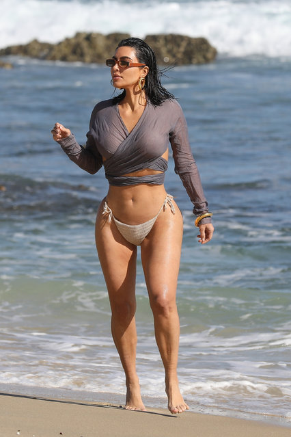 Donning a wet long sleeve crop top with string beige bikini bottoms, Kim Kardashian, 39, the mom of four flaunted her hourglass figure while walking down the beach in Malibu on September 10, 2020. (Photo by BackGrid/The Sun)