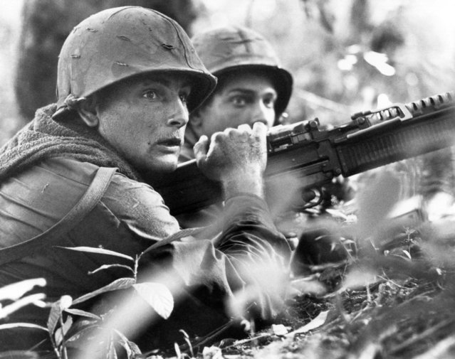 U.S. machine gunner Spc. 4 James R. Pointer, left, of Cedartown, Ga., and Pfc. Herald Spracklen of Effingham, Ill., peer from the brush of an overgrown rubber plantation near the Special Forces camp at Bu Dop during a half hour firefight, December 5, 1967. Their company-size patrol avoided an ambush when a patrol dog alerted the unit to the presence of enemy forces. (Photo by Horst Faas/AP Photo)