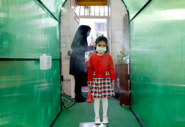 An Iranian elementary school girl wearing a face mask passes by a disinfection tunnel as she attends the first day of reopening the Bamdad Parsi private school, north of Tehran, Iran, 05 September 2020. Media reported that school has reopened in Iran during the coronavirus crisis in the country. (Photo by Abedin Taherkenareh/EPA/EFE)
