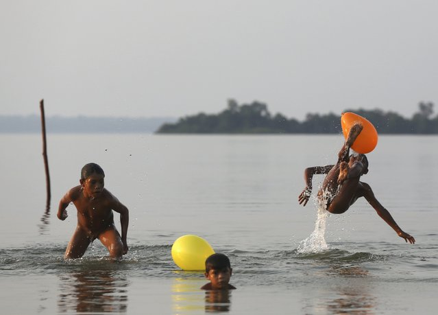 Indigenous children from the Kamayura tribe play with balloons in Ipavu lake at Xingu national park in Mato Grosso, Brazil, October 3, 2015. (Photo by Paulo Whitaker/Reuters)