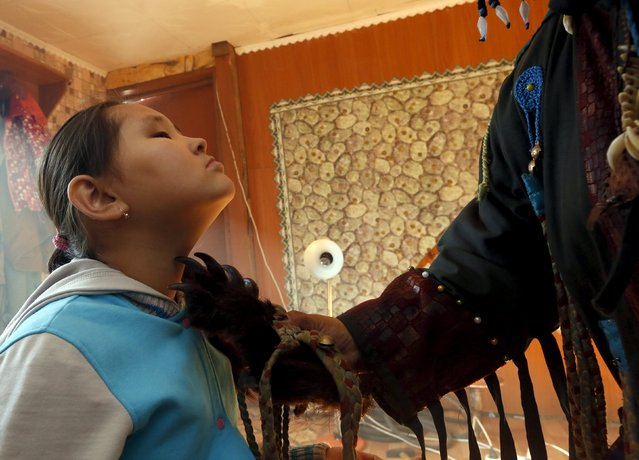 A female shaman Saida Mongush uses a paw of a bear as she conducts a medical session to cure a 9-year-old girl Norzhunmaa, who suffers from spinal curvature as a result of a patrimonial trauma, at her house in the town of Kyzyl, the administrative centre of Tuva region, Southern Siberia, Russia, October 7, 2015. The region is inhabited by Tuvans, historically cattle-herding nomads, who nowadays practise two main confessions – Buddhism and Shamanism. (Photo by Ilya Naymushin/Reuters)