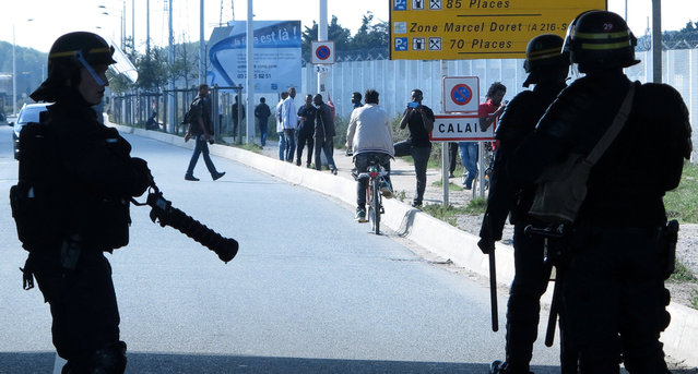 "French riot policemen stand guard at the entrance of the ""Jungle"" as dozens of migrants try to storm lorries which are heading towards the ferry terminal in Calais, France, September 21, 2016. (Photo by Pascal Rossignol/Reuters)"