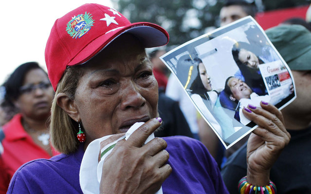 With photo in hand of Hugo Chavez, Venezuelan weeps after the announcement of the death of the country's president. (Photo by Carlos Garcia Rawlins/Reuters)
