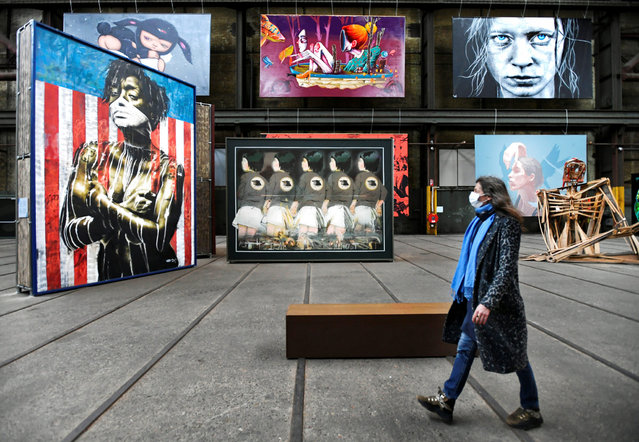 A woman wearing a mask looks at street art as she walks at the International Street Art Museum following the new social restrictions announced by the Dutch government, as the Netherlands battle to control the spread of the coronavirus disease (COVID-19), in Amsterdam, Netherlands on October 14, 2020. (Photo by Piroschka van de Wouw/Reuters)