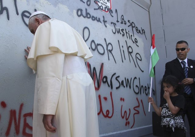 Pope Francis touches the wall that divides Israel from the West Bank, on his way to celebrate a mass in Manger Square next to the Church of the Nativity in the West Bank city of Bethlehem, in this May 25, 2014 file photo. (Photo by Mheisen Amareen/Reuters)