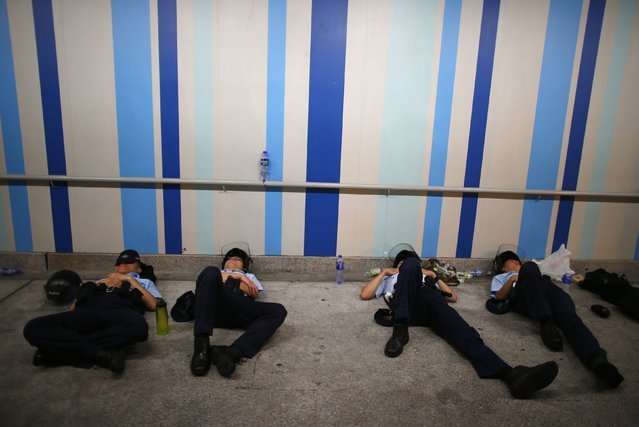 Police officers sleep as protesters (not pictured) block the main street to the financial Central district outside the government headquarters in Hong Kong, in this September 29, 2014 file photo. (Photo by Carlos Barria/Reuters)