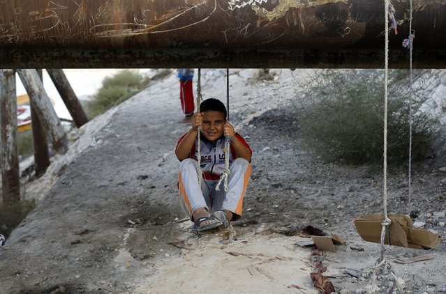 A boy plays under a pipe in the fishermen's village in the El Max area of the Mediterranean city of Alexandria October 18, 2014. (Photo by Amr Abdallah Dalsh/Reuters)