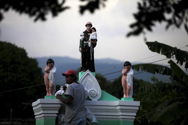 A man decorates a grave during All Saints day in Nahuizalco on November 1, 2015. People visit the cemeteries and graves of deceased relatives and friends to commemorate All Saints Day, which falls on November 1. (Photo by Jose Cabezas/Reuters)
