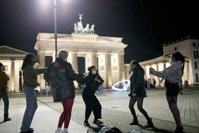 Women dance to celebrate the victory of President-elect Joe Biden and Vice President-elect Kamala Harris in front of the Brandenbug Gate next to the United States embassy in Berlin, Germany, Saturday, November 7, 2020. Biden defeated President Donald Trump to become the 46th president of the United States on Saturday, positioning himself to lead a nation gripped by the historic pandemic and a confluence of economic and social turmoil. (Photo by Markus Schreiber/AP Photo)