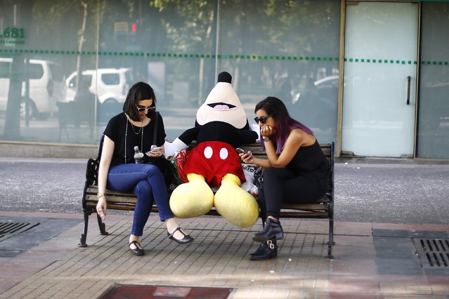 Women use their mobile phones next to a stuffed Mickey Mouse toy as they sit in a bench outside a commercial mall in Santiago city, December 10, 2014. (Photo by Ivan Alvarado/Reuters)