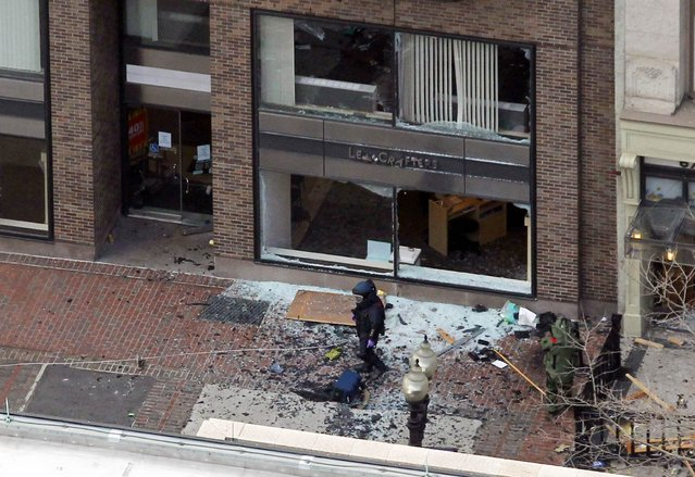 A man in a bomb-disposal suit investigates the site of an explosion which went off on Boylston Street during the 117th Boston Marathon in Boston, Massachusetts April 15, 2013. (Photo by Jessica Rinaldi/Reuters)