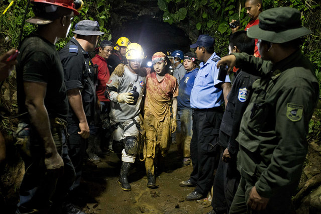 In this August 29, 2014 file photo, young miner Leber Vivas Gonzales, 16, center right, walks with his his arm over the shoulders of a rescue worker after he was saved from the El Comal gold and silver mine in Bonanza, Nicaragua. Rescuers saved 22 of at least 26 workers trapped after a mine collapse. (Photo by Esteban Felix/AP Photo)