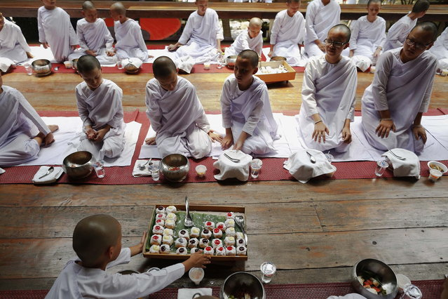 Doughnuts are served with other food as novice nuns have their lunch at the Sathira-Dhammasathan Buddhist meditation centre in Bangkok April 21, 2013. A group of Thai girls are choosing to spend part of their school holidays as Buddhist nuns, down to having their heads shaven at the meditation centre. The centre, founded in 1987, is a learning community for peace and harmony that has programs open to people regardless of age and gender. (Photo by Damir Sagolj/Reuters)