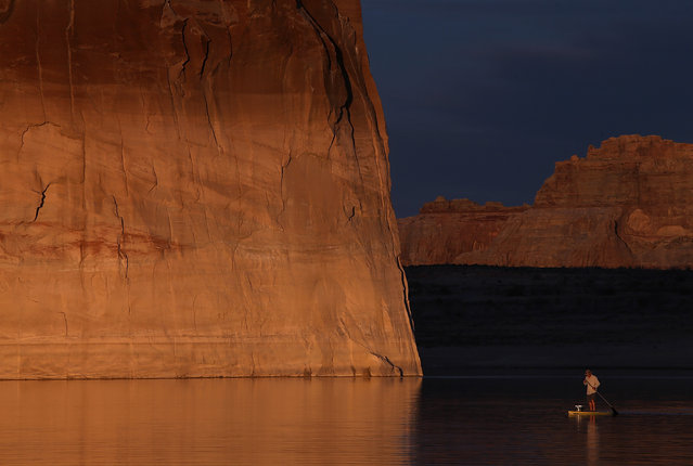 A paddleboarder floats by Lone rock on Lake Powell on March 29, 2015 near Big Water, Utah. (Photo by Justin Sullivan/Getty Images)
